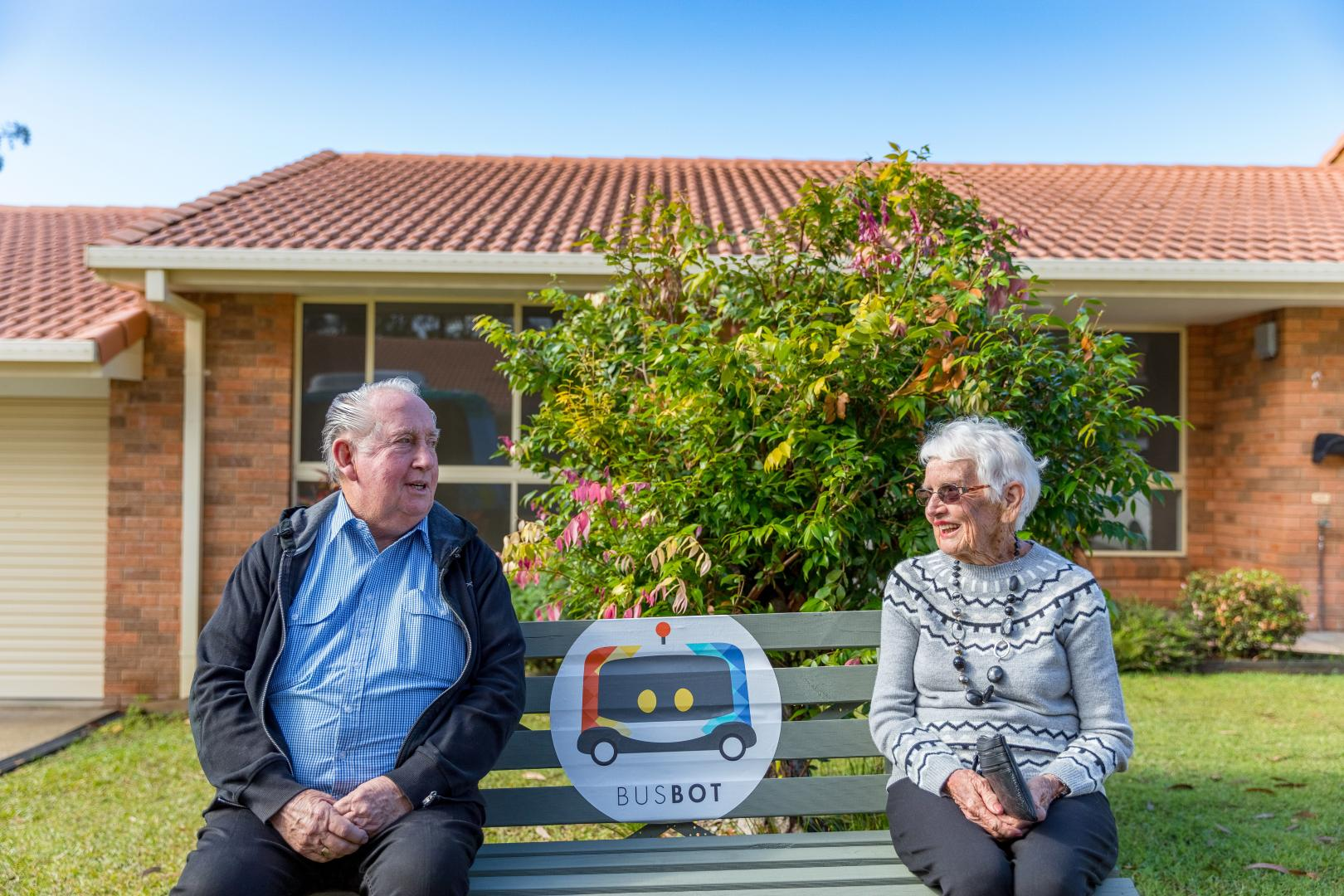 Residents Margaret and Keith enjoying a the sunshine at the BusBot bus stop. Photo: Mitchell Franzi